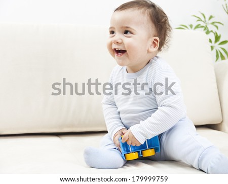 baby playing with a toy car on the couch - stock photo