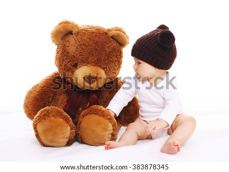 Baby playing with big teddy bear toy on white background - stock photo