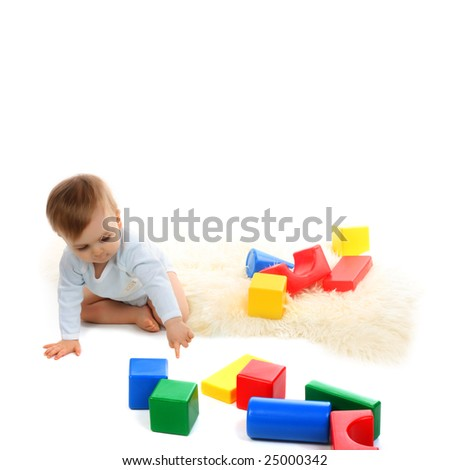 Baby playing with bright blocks on white background - stock photo