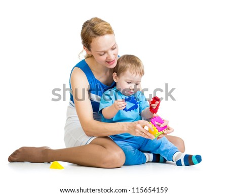 baby playing with colourful cup toys on floor, isolated on white - stock photo