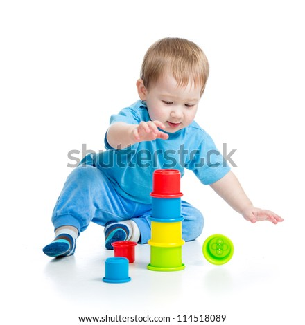 baby playing with colourful cup toys on floor, isolated over white - stock photo