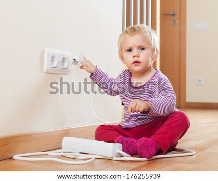 Baby playing with electrical extension and outlet on floor   - stock photo