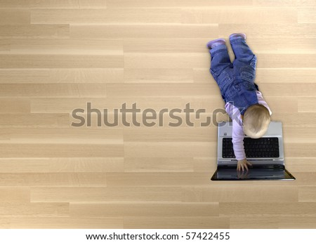 baby playing with laptop on wood floor with lots of copy space - stock photo