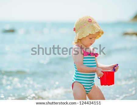 Baby playing with pail near sea - stock photo