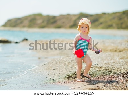 Baby playing with pail on sea shore - stock photo