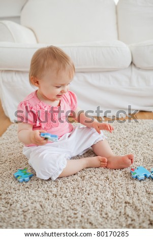 Baby playing with puzzle pieces while sitting on a carpet in the living room - stock photo
