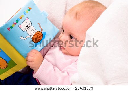 Baby playing with story book sitting in baby carrier. - stock photo