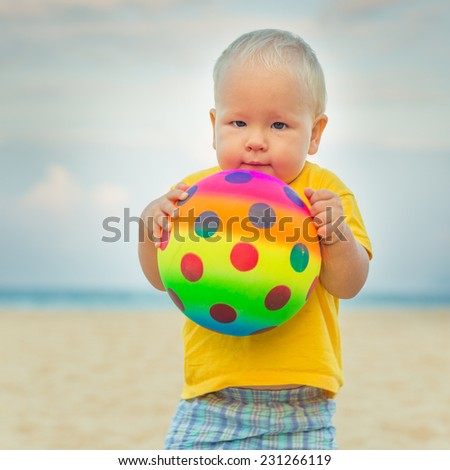 Baby playing with toy ball - stock photo