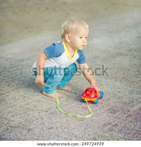 Baby playing with toy car - stock photo