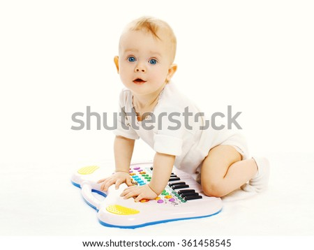 Baby playing with toy piano on a white background - stock photo