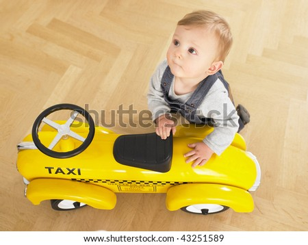 Baby playing with toy taxi cab car. Horizontally framed shot. - stock photo