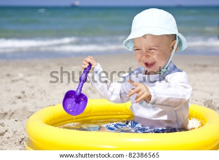 baby playing with toys in pool on a beach