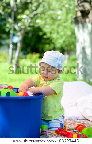 baby playing with toys in the garden