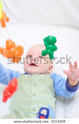 Baby playing with toys. Little boy touching the toys by finger - stock photo