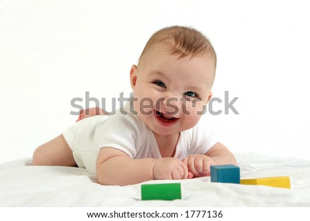 Baby playing with wooden blocks and smiling at the camera. - stock photo
