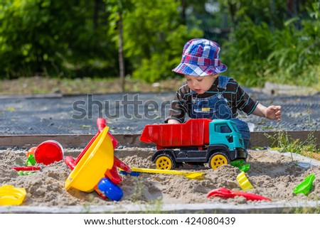 baby plays in sandbox - stock photo