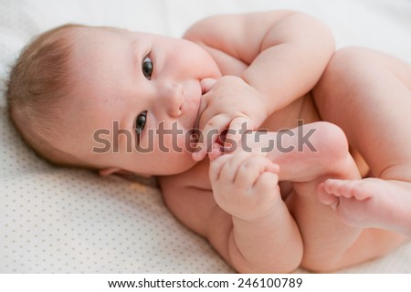 Baby plays with own feet - stock photo