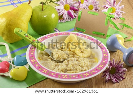 Baby porridge with fruit and greeting card - stock photo