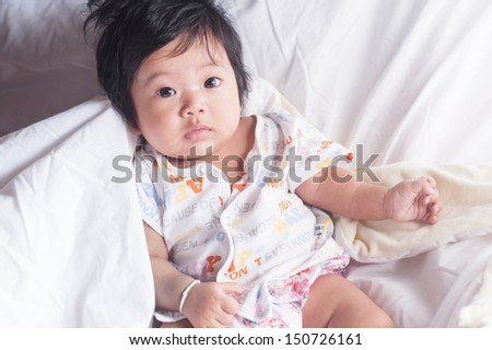 Baby Portrait looking straight at you lying on white blanket