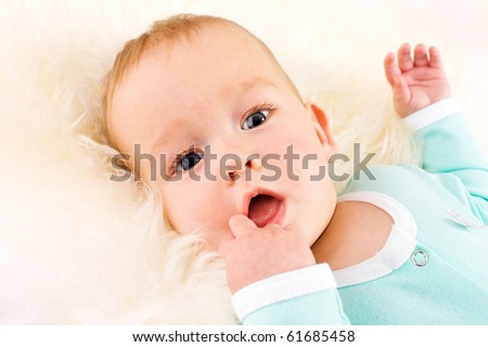 Baby Portrait looking straight at you lying on white fluffy fur - stock photo