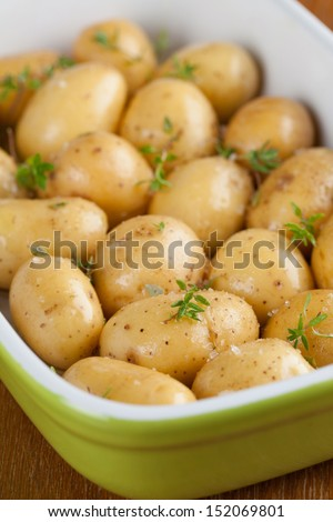 Baby potatoes with thyme, olive oil and salt on baking sheet - stock photo