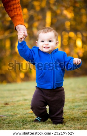 Baby practicing walking outdoors on fall day - stock photo