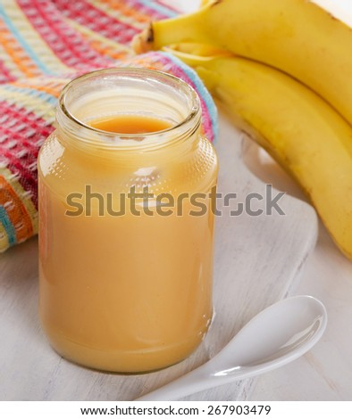 Baby puree in a glass jar with bananas. Selective focus - stock photo