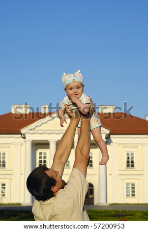 baby raised up in hands of the father relating to the house of the palace - stock photo