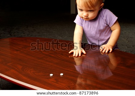 Baby reaching across coffee table at white pills - stock photo