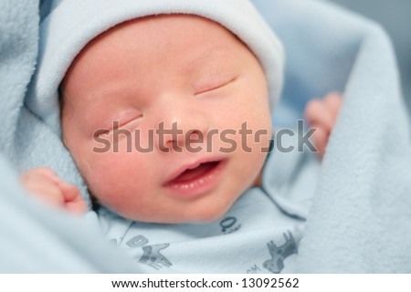 Baby resting with a peaceful expression on face surrounded in light blue blankets