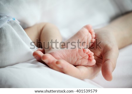 Baby's Feet in Mother Hand Closeup - stock photo