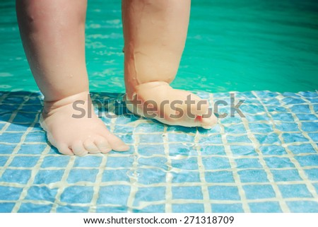 Baby's feet in swimming pool - stock photo