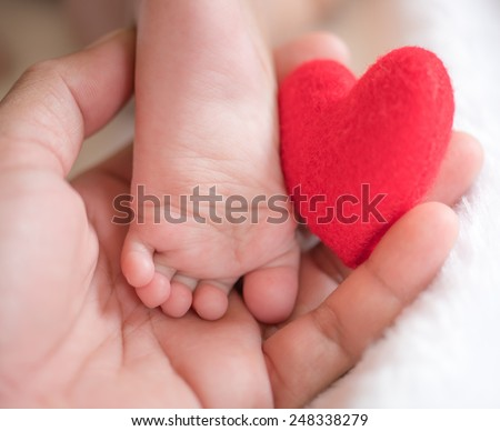 baby's feet with a red heart - stock photo
