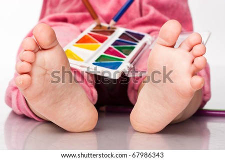 Baby's feet with paint and pencils isolated on white - stock photo