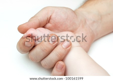 baby`s  feets holding a father`s finger