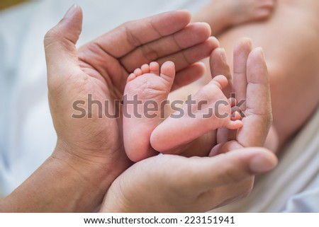 Baby's foot in mother hands - stock photo