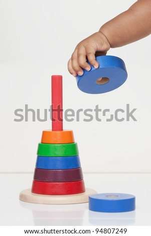Baby's hand holding a wooden toy, demonstrating fine motor skill - stock photo