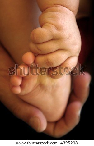 Baby's hand holding his foot and father's hand holding all - stock photo