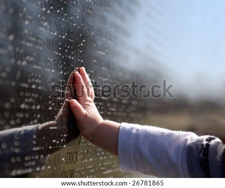Baby's Hand on Vietnam Memorial - stock photo