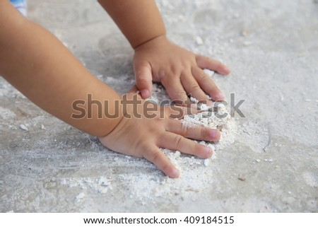baby's hand playing dry cassava dust on the ground