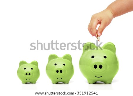 baby's hand putting a golden coin into green piggy bank with small, medium, and large size - young generation doing green saving concept