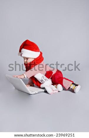 baby santa claus with white laptop - stock photo