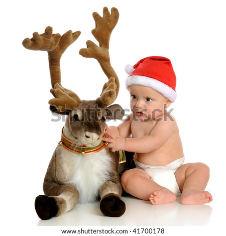 Baby Santa fixing a plush reindeer's collar.  Isolated on white. - stock photo