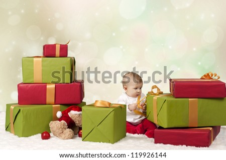 baby seated on a stack of christmas presents, on bokeh background