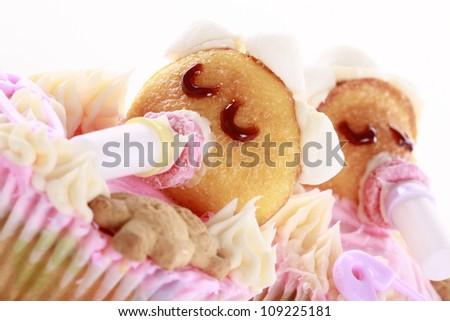 Baby shaped cupcakes - Shallow DOF - Focus on caramel eyelashes - stock photo