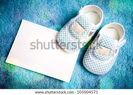 Baby shoes and empty postcard in vivid light style