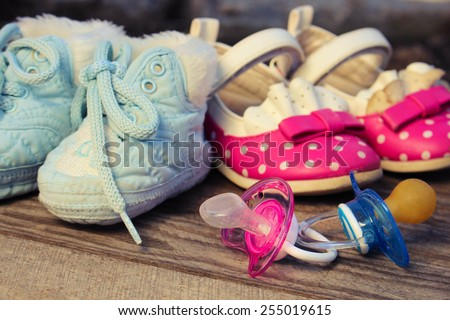 Baby shoes and pacifiers pink and blue on the old wooden background. Toned image.  - stock photo