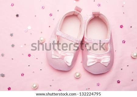 Baby shoes for a girl on pink blanket with pearls - stock photo