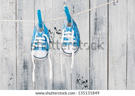 Baby shoes hanging on the clothesline. - stock photo