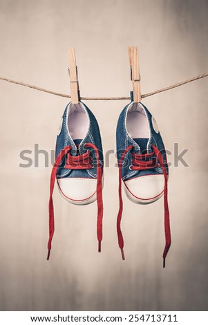Baby shoes hanging on the clothesline - stock photo
